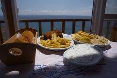Greek food. Typical greek food on a terrace with an great view to the ocean Royalty Free Stock Photography