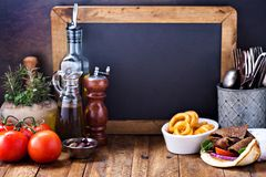 Greek food concept background. Greek food background with gyro pita, curly fries and chalkboard copy space Stock Images