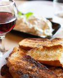 Greek food, roasted bread with olive oil and herbs, red wine and tzatziki sauce. Served in cafe stock images