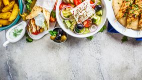 Greek food: greek salad, chicken souvlaki, gyros and baked potato wedges on gray background, top view. Traditional greek cuisine