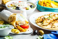 Greek food: salad, chicken souvlaki, gyros and baked potatoes on gray background. Traditional greek cuisine concept