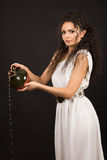 Greek girl with jug. Curly girl in a Greek toga pouring water from a jug Stock Photography