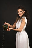 Greek girl with jug. Curly girl in a Greek toga pouring water from a jug Royalty Free Stock Photography