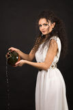 Greek girl with jug. Curly girl in a Greek toga pouring water from a jug Royalty Free Stock Images