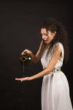 Greek girl with jug. Curly girl in a Greek toga pouring water from a jug Royalty Free Stock Image