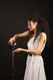 Greek girl with jug. Curly girl in a Greek toga pouring water from a jug Stock Photos