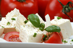 Greek goat cheese with tomato and basil Stock Photo