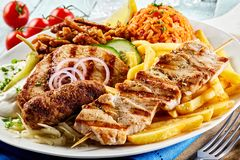 Greek grill plate with assorted meats. Crispy potato chips, tomato rice pilaf and raiti in a close up view suitable for a menu stock photo