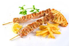 Greek grilled pork souvlaki sandwich junk food kalamaki. Greek pork grilled souvlaki sandwich with potatoes and vegetables Stock Photo
