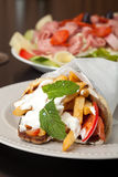 Greek Gyro and Antipasto Salad. Traditional Gyro sandwich with meat  tzatziki sauce tomato onions and fried potato garnished with mint. Shallow depth of field Royalty Free Stock Image