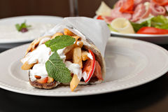 Greek Gyro Wrap. Traditional Gyro sandwich with meat  tzatziki sauce tomato onions and fried potato garnished with mint. Shallow depth of field Stock Photo