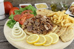 Greek gyros. Plate of traditional Greek gyros with meat, fried potatoes, tomato and onion Royalty Free Stock Image