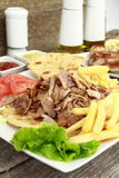 Greek gyros. Plate of traditional Greek gyros or Turkish kebab with meat, fried potatoes, tomato and onion Royalty Free Stock Photos