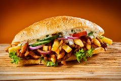 Greek gyros burger with roasted sliced meat. Lettuce, onion, cucumber, tomato and French fries on a fresh bread roll on rustic wood royalty free stock images