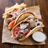 Greek gyros with tzatziki sauce. And fries on parchment Stock Image