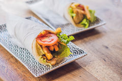 Greek gyros wrapped in a pita bread on a wooden background stock image