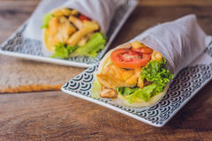 Greek gyros wrapped in a pita bread on a wooden background royalty free stock photo