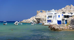 Greek homes by the sea. Greek homes and church built on a rocky site with white cliffs beside turquoise blue waters royalty free stock image