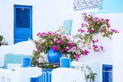 Greek House with Blue Door and Colorful Flowers Stock Photo