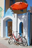 Greek House with Umbrella and Bicycle. Blue and white painted Greek house decorated with umberlla and bicycle in Kos Island,Greece stock image