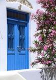 Greek island ancient building door with flowers. Old greek island wood door with cyclades architecture flowering tree ancient construction Stock Photos