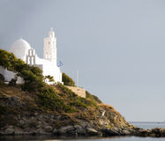 Greek island church Ios Cyclades island. Classic white church with Greek flag at mouth of harbor Ios Cyclades island Greece Stock Images