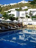 Greek Island Hotel Swimming Pool, Skyros, Greece. Typical white Greek island houses reflected in the blue water of a hotel swimming pool, Skyros, a Spoades group Royalty Free Stock Photography