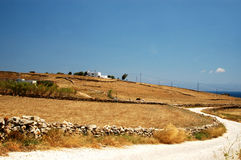 Greek island landscape. A landscape in the greek islands with a winding road and a typical greek house in the distance Royalty Free Stock Image