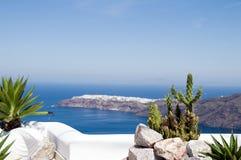 Greek island mediterranean view santorini. Plants and cactus on cliff ledge overlooking caldera and the mediterranean sea view of oia on greek island of Royalty Free Stock Photo