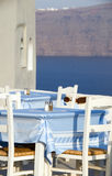 Greek island restaurant furniture view caldera. Typical classic woven chairs in Greek Island restaurant with romantic view of volcanic caldera cliffs in Oia Stock Image