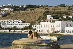 Greek island scene in harbor. Greek island harbor scene with girls on old fishing boat and typical cyclades architecture stock images