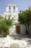 Greek island scene old church. Greek island street scene old church with cyclades architecture tile painted street with flowers trees Royalty Free Stock Images