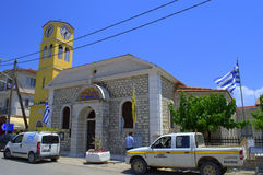 Greek island street church. Orthodox church on Nydri main street and maintenance cars of Greek Telecommunications provider OTE ,Lefkada island,Greece. Nydri is Stock Photo
