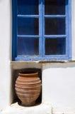 Greek island window scene. Old greek island wood frame window with ceramic vase greece street scene Stock Image