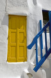 Greek islands doors. A old yellow doorand a yellow staircase railing in Mykonos,  Greece Stock Image