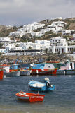Greek Islands Series - Mykonos. View of the harbor in Mykonos with lots of colorful boats parked and a hill with signature white houses and shops. Part of a Stock Photo