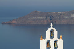 Greek Islands Series - Santorini. Church bells and cross in the foreground with one of the Santorini islands in the background, focus on the church with the rest Stock Photography