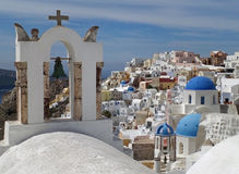 Greek Islands style white bell-tower and blue domes of the church at Oia village, Santorini island Royalty Free Stock Image