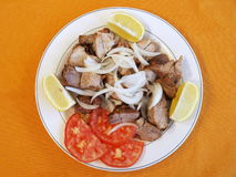 Greek Kebab. Plate with Greek kabob meat garnished with lemons and tomatoes royalty free stock photography