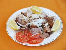 Greek Kebab. Meats on a plate with lemon wedges and sliced tomatoes royalty free stock images