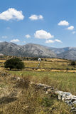 Greek landscape with meadow, mountain and blue sky, white chapel Royalty Free Stock Photo