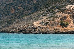 Greek landscape - rocky mountain and Aegean sea. Greek landscape with a sandy road in a rocky mountain with rear green bushes and Aegean sea in the foreground stock images