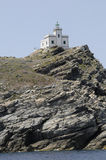 Greek lighthouse on top of rocky cliff at Paros Greece Stock Images