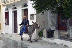 Greek man on donkey in the picturesque town of Plomari Stock Images