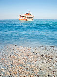 Greek marble beach, blue sea and cruise boat Stock Photo
