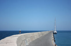 Greek Marina. The girl in a hat goes to the yacht on a mooring Stock Photos