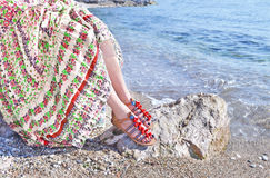 Greek model advertises bohemian sandals and clothes at the beach. Greek fashion clothes advertisement stock images