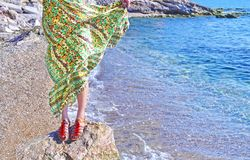 Greek model advertises bohemian sandals and clothes at the beach. Greek fashion clothes advertisement stock photography