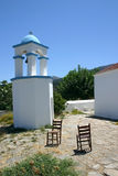 Greek Monastery Scene. Tower of Greek Monastery with chairs in front Royalty Free Stock Photo