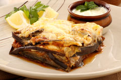 Greek Moussaka. Delicious Greek moussaka with aubergine and a side garden salad stock photos